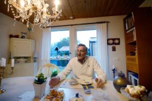 Hemma i radhusvillan bjuder Svenny Håkansson på tårta och kaffe. – Vi måste kunna umgås, även om vi har olika åsikter, säger han. (Foto: Stefan Mattsson)